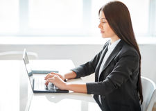 Stående av den nätta affärskvinnan med bärbara datorn i det offic Royaltyfri Fotografi