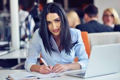 Stående av den nätta affärskvinnan som arbetar i det upptagna kontoret och blickarna, medan göra en anmärkning på anteckningsboke arkivbild