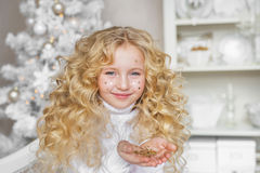 Stående av den nätta blonda lilla flickan med en konfetti på framsida och på händer i jul Royaltyfri Fotografi