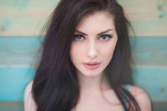 Stående av den nätta caucasian flickan med blåa ögon på färgrik träbakgrund Arkivfoto