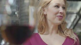 Stående av den nätta eleganta blonda kvinnan med lockigt hår som talar med vännen i bakgrunden av suddigt exponeringsglas av  lager videofilmer