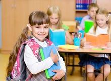 Stående av den nätta förskole- flickan med böcker i klassrum Arkivbilder