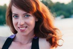 Stående av den nätta flickan som ler riktigt, på sommarnaturbackgrou arkivfoton