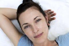 Stående av den nätta kvinnan som ligger och poserar Arkivfoton