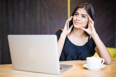 Stående av den nätta kvinnan som talar med dåliga sinnesrörelser på telefonen, medan sitta i kafét och tycka om kaffe Royaltyfri Fotografi