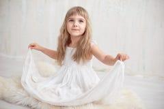Stående av den nätta lilla flickan i den vita klänningen som ser kameran och att le som står mot grå bakgrund royaltyfria bilder