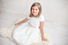 Stående av den nätta lilla flickan i den vita klänningen som ser kameran och att le som står mot grå bakgrund Fotografering för Bildbyråer