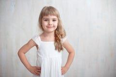 Stående av den nätta lilla flickan i den vita klänningen som ser kameran och att le som står mot grå bakgrund royaltyfri fotografi