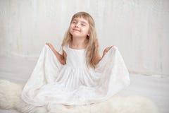 Stående av den nätta lilla flickan i den vita klänningen som ser kameran och att le som står mot grå bakgrund arkivfoto