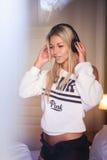 Stående av den nätta lyckliga flickan med hörlurar som lyssnar till popmusik arkivfoton