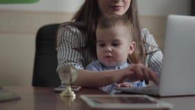 St?ende av den n?tta modern och lilla sonen som inomhus placeras med en b?rbar dator p? tabellen Upptagen ung moder som hemma arb arkivfilmer