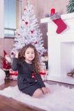 Stående av den nätta söta lilla flickan nära en spis i jul Arkivbild