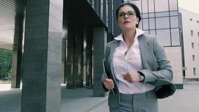 Stående av den nätta unga affärskvinnan som kör till kontorsbyggnaden arkivfilmer