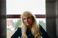 Stående av den nätta unga blondinen i hissen Fotografering för Bildbyråer