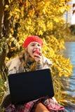 Stående av den nätta unga flickan i röd hatt som äter ett äpple och le fotografering för bildbyråer