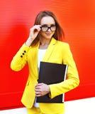 Stående av den nätta unga kvinnan i exponeringsglas, gul dräkt Arkivfoton