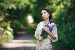 Stående av den nätta unga kvinnan som går i en felik skog med buketten av blommor Royaltyfri Foto
