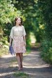 Stående av den nätta unga kvinnan som går i en felik skog med buketten av blommor Royaltyfria Foton