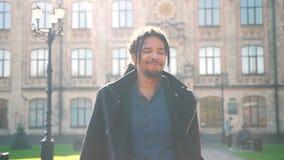 Stående av den nöjda afrikansk amerikanstudenten med dreadlocks som går i solsken från universitet och hälsar någon lager videofilmer