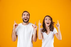 Stående av den nöjda den folkmannen och kvinnan i grundläggande bekläda peka fingrar, medan stå tillsammans isolerat över guling arkivfoton