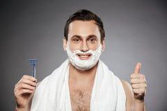 Stående av den nöjda mannen med att raka skum på hans hållande rommar för framsida Royaltyfri Fotografi