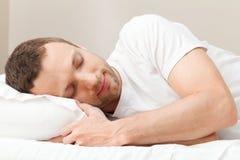Stående av den nöjda sova unga mannen i vit arkivbilder