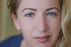 Stående av den naturligt härliga kvinnan i hennes tjugotal med blont hår och blåa ögon, skott utanför i naturligt solljus arkivfoto