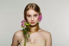 Stående av den nya och härliga blonda flickan med rosa blommor arkivbilder