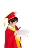 Stående av den nyfikna pojken i röd kappaungeavläggande av examen med Mortarbo Arkivbilder