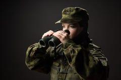 Stående av den obeväpnade kvinnan med kamouflage Den unga kvinnliga soldaten observerar med kikare Arkivbilder