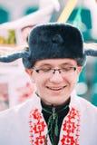 Stående av den okända lyckliga unga mannen i rolig nationell ryssfolkkläder Fotografering för Bildbyråer