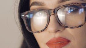 Stående av den passionerade flickan i exponeringsglas med stora ögon och röda kanter långsamt lager videofilmer