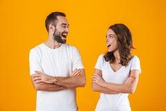 Stående av den positiva den folkmannen och kvinnan i grundläggande kläder som ler, medan stå tillsammans isolerat över gul bakgru royaltyfri fotografi