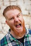 Stående av den röda haired mannen som uttrycker en sinnesrörelse Arkivfoton