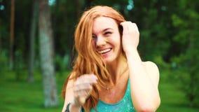 Stående av den röda haired unga kvinnan som skrattar på kameran efter den Holi festivalen lager videofilmer