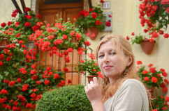 Stående av den rödhåriga kvinnan framme av röda blommor Royaltyfri Bild
