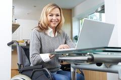 Stående av den rörelsehindrade kvinnan i rullstol genom att använda bärbara datorn hemma fotografering för bildbyråer