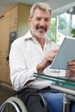 Stående av den rörelsehindrade mannen i rullstol genom att använda den Digital minnestavlan på H royaltyfri foto