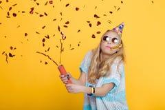 Stående av den roliga blonda kvinnan i födelsedaghatt och röda konfettier på gul bakgrund Beröm och parti royaltyfri bild
