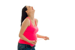 Stående av den roliga gravida brunetten i rosa skratta för skjorta som isoleras på vit bakgrund Arkivfoto