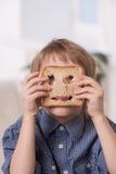 Stående av den roliga pojken som spelar med bröd royaltyfri foto