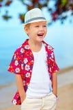 Stående av den roliga skratta pojken på stranden Arkivfoto