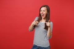 Stående av den roliga unga kvinnan i randig kläder som skriker som pekar pekfingrar på kameran som isoleras på den ljusa röda väg royaltyfri foto