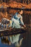 Stående av den romantiska kvinnan i en klänning på banken av floden Royaltyfri Foto
