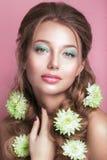 Stående av den romantiska unga kvinnan med den gröna blomman och makeup som ser kameran Vårmodefoto Royaltyfri Fotografi