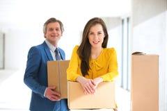 Stående av den säkra affärskvinna- och mankollegan med kartonger i nytt kontor Arkivfoton