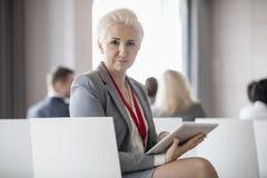 Stående av den säkra affärskvinnan som rymmer den digitala minnestavlan, medan sitta i seminariumkorridor arkivfoto