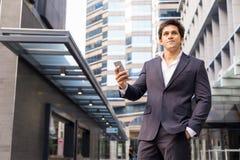 Stående av den säkra affärsmannen med mobiltelefonen utomhus Arkivfoton