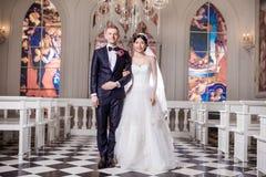 Stående av den säkra armen för bröllopparanseende i arm på kyrkan Arkivfoton