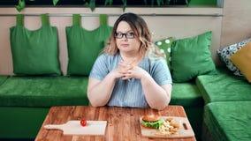 Stående av den säkra banta feta kvinnan som räknar kalorier som väljer mellan sunt vs sjukligt mål stock video